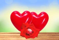 红色心脏和在明亮的自然的木桌上上升了 库存图片