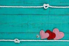 红色心脏和心脏由绳索边界锁反对小野鸭蓝色木背景 免版税库存照片