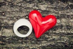 红色心脏和白色圆环在树皮 免版税库存照片