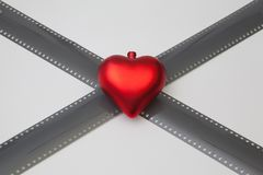 红色心脏和被展开的被暴露的35mm影片小条 免版税库存图片