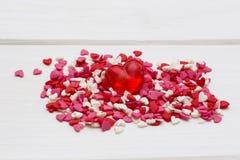 红色心脏和许多更小的心脏在白色木背景 免版税库存图片