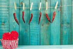 红色心脏和辣椒在木背景 节假日背景 重点 免版税库存图片