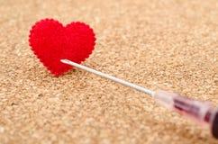 红色心脏和针注射器 免版税库存照片