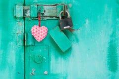红色心脏在与锁的一个门垂悬 库存照片