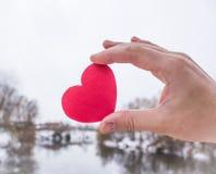 红色心脏在女孩的手上 河背景 库存照片