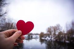 红色心脏在女孩的手上 河背景 图库摄影