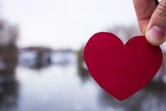 红色心脏在女孩的手上 河背景 免版税库存图片