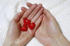 红色心脏在女性手上 库存照片