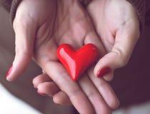 红色心脏在妇女手上,爱的标志 免版税库存照片