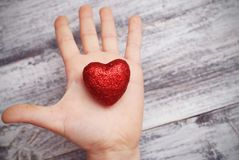红色心脏在手上举行了由孩子被隔绝在白色和黑背景 日s华伦泰 母亲和妇女` s天 免版税库存照片