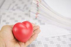 红色心脏在手中有迷离堆文书工作作为背景 免版税库存图片
