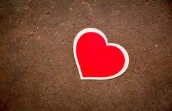 红色心脏在混凝土说谎 库存图片