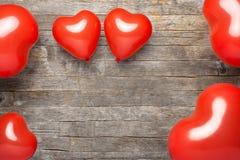 红色心脏在老木桌,华伦泰` s天背景上迅速增加 库存图片