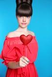 红色心脏在青少年的女孩手上 与弓头发的深色的年轻模型 图库摄影