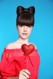 红色心脏在青少年的女孩手上 与弓头发的深色的年轻模型 库存照片
