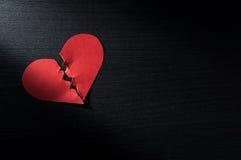 红色心脏在黑暗的木头的被弄皱的纸 图库摄影