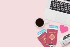 红色心脏平的位置在两护照,咖啡,计算机膝上型计算机的 免版税库存照片
