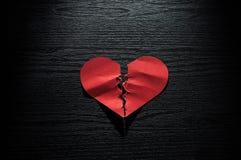 红色心脏弄皱了在黑暗的木背景的纸 免版税库存图片