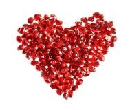 红色心脏形状由石榴种子制成 免版税库存图片