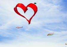 红色心脏形状风筝在蓝天飞行 库存图片
