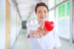 红色心脏由微笑的女性护士` s手举行了,代表给努力优质服务头脑患者 专业人员 库存图片
