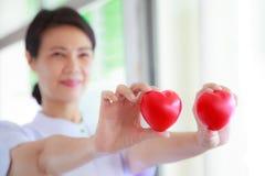 红色心脏由微笑的女性护士` s手举行了,代表给努力优质服务头脑患者 专业人员 库存照片