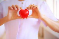 红色心脏由微笑的女性护士` s手举行了,代表给努力优质服务头脑患者 专家, Spec 图库摄影