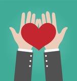 给红色心脏的商人手 免版税库存图片