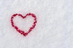 红色心脏的形状在雪的在冬天, 2月14日- 库存照片