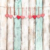 红色心脏装饰垂悬的情人节贺卡 图库摄影