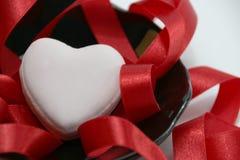 红色心脏,在黑盘子的红色丝带 库存照片