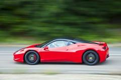 红色快速地驾车在乡下公路 免版税库存图片