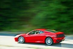 红色快速地驾车在乡下公路 库存图片