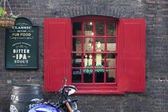 红色快门和在圣诞节前装饰的客栈窗口 免版税库存图片