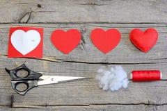 红色感觉心脏,削减在心脏的形状,纸样式,剪刀,螺纹,在一张木桌上的针的毛毡零件 毛毡心脏工艺 免版税库存图片