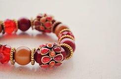 红色成串珠状镯子 免版税库存照片