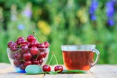 红色成熟樱桃结果实与在玻璃碗和杯子的花梗t 免版税库存图片