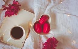 红色或桃红色macarons顶视图在一朵心形的碗、咖啡、书和花的 免版税库存照片