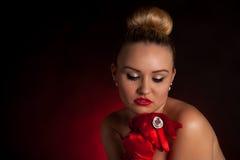红色手套和一个大圆环的性感的年轻白肤金发的妇女 免版税库存照片