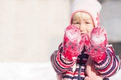 红色手套的小女孩有白色心脏的显示手 免版税库存照片