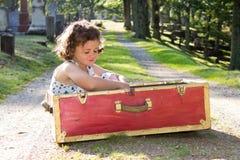 红色手提箱的孤儿女孩 库存照片