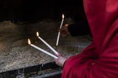 红色打扮了点燃三个蜡烛的妇女祝愿运气 免版税库存图片