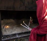 红色打扮了点燃三个蜡烛的妇女祝愿运气 免版税图库摄影