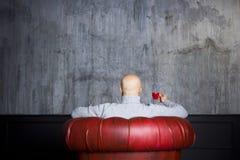 红色扶手椅子的秃头人 库存图片