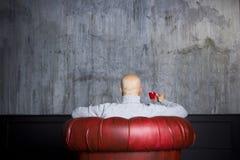 红色扶手椅子的秃头人 免版税图库摄影
