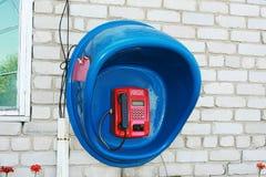 红色投币式公用电话在蓝色摊 免版税库存图片