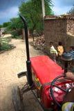红色拖拉机和连续孩子 库存图片