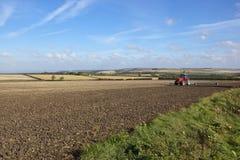 红色拖拉机和风景 免版税库存图片