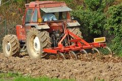 红色拖拉机在工作 免版税库存照片