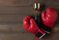 红色拳击手套和战利品在木bcakground 免版税库存照片